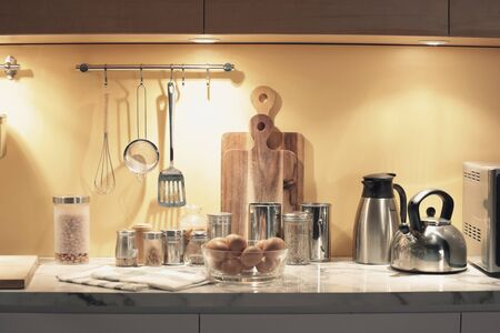 some kitchenwares and ingredient bottles put on the counter and hanging on the wall