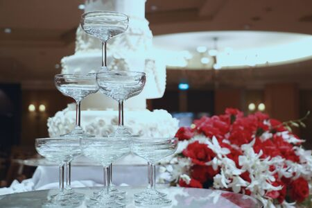 the champagne tower put near by big layer cake in the center of wedding party hall 스톡 콘텐츠