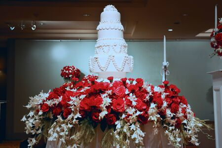 a big 4 layers wedding cake stand on a table of flowers in center of hall for party
