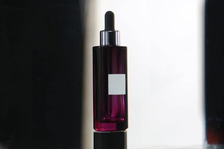a packaging shot of purple glass cosmetic bottle shooting in studio 스톡 콘텐츠