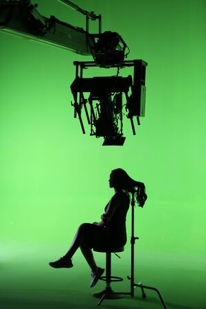 a woman is sitting on green screen show her hair under a cinema camera on the crane
