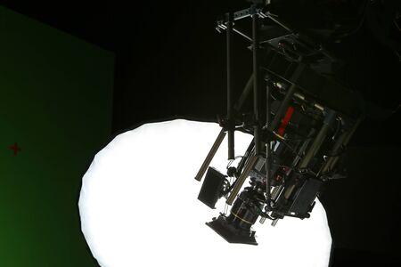 a cinema camera setup on crane and lift up above a big umbrella light in studio