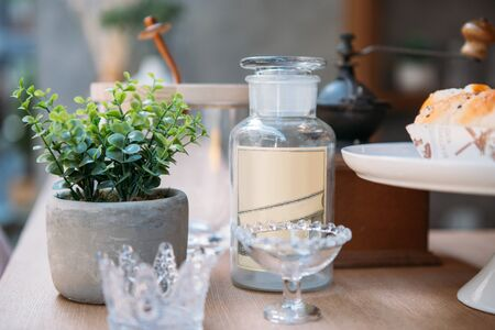 a vintage glass bottle put near by a decoration plant pot and other stuffs on the coffee counter bar 스톡 콘텐츠