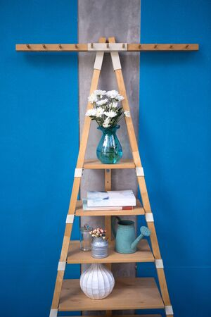 some decoration stuffs put on a wooden triangle ladder shelf on the blue wall 免版税图像