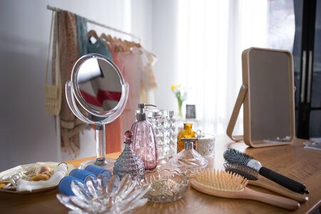 many beauty accessories put on a dressing table and clothes rack in woman room