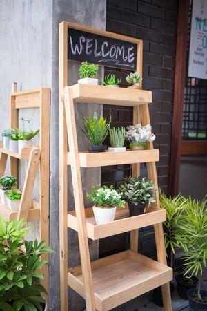 many pots of decoration plants put on the wooden shelfs in tree shop on sidewalk street 스톡 콘텐츠
