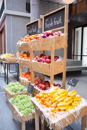 a lot of grape, orange, apple and star fruit put in wooden tray and shelf on sidewalk street shop 스톡 콘텐츠