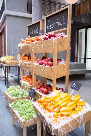 a lot of grape, orange, apple and star fruit put in wooden tray and shelf on sidewalk street shop 免版税图像