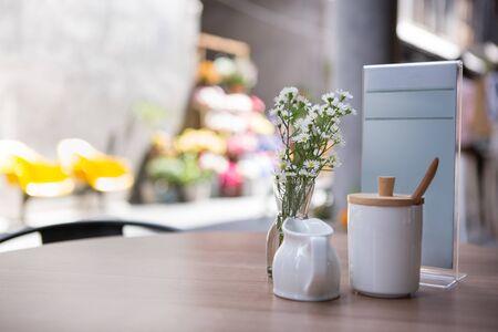 white ceramic milk mug and sugar jar put with menu stand on a table of sidewalk cafe 스톡 콘텐츠