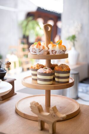 a three level wooden cake stand and some dessert put on the counter bar in sidewalk cafeteria