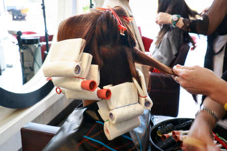 hairdresser straight some hair prepare for rolling with a rod for perming step in salon