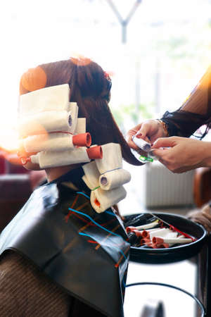 some hair prepared rolling with rods for perming step in salon