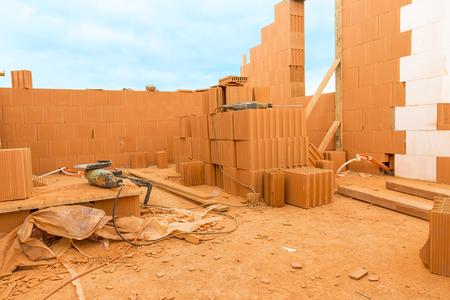 materiales de construccion: Ladrillo a ladrillo, construir una casa por su cuenta. La construcci�n de una casa. Las herramientas el�ctricas en el sitio de construcci�n polvoriento. Casa en construcci�n
