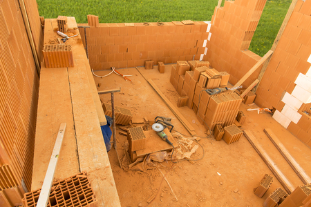 Brick by Brick,  build a house on your own. Building a home. Power tools on the dusty construction site. House under construction photo