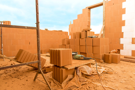 build in: Brick by Brick,  build a house on your own. Building a home. Power tools on the dusty construction site. House under construction