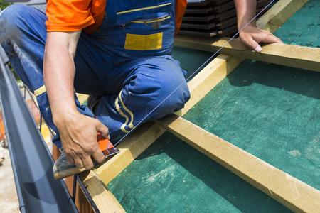 Un techador en la azotea prepairing construcción de madera. La medición con mayor precisión.
