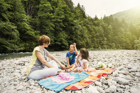 single family: Family picnic by the river. Rapids and the forest in the background Stock Photo
