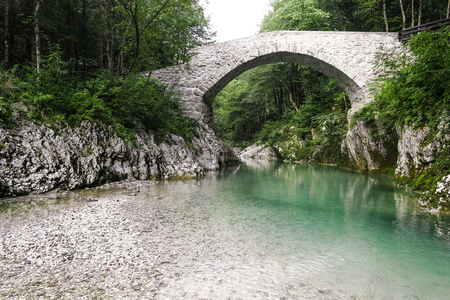 emerald stone: Beautiful wild river in the national park. Emerald color river flows through unspoiled nature. Wilderness all around. Ancient stone bridge. Stock Photo