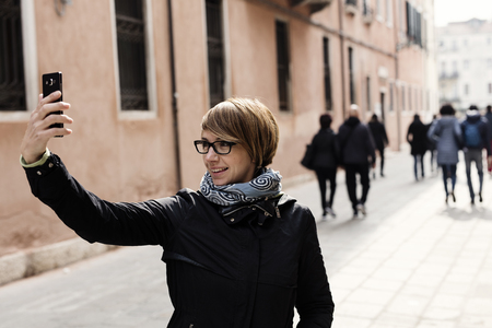 narcissistic: Traveling around the world. Beautiful modern woman making selfie. Local sights in the background.