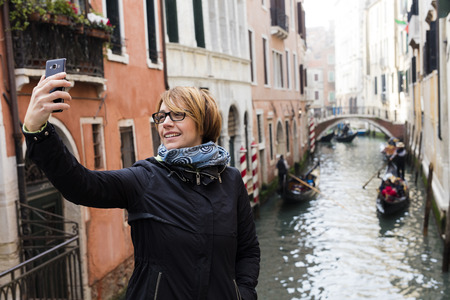 narcissistic: Traveling around the world. European cities. Beautiful modern woman making selfie. Local sights in the background. Stock Photo
