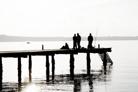 socializando: Los pescadores locales capturan peces desde el muelle. Los locales que ofrecen pescado fresco, calamares, pulpos y sepias para los restaurantes de lujo. Con los amigos. Foto de archivo