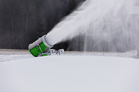spews: Making snow on the ski track. Artificial snow in the ski resort. Snow machine spews snow. Stock Photo