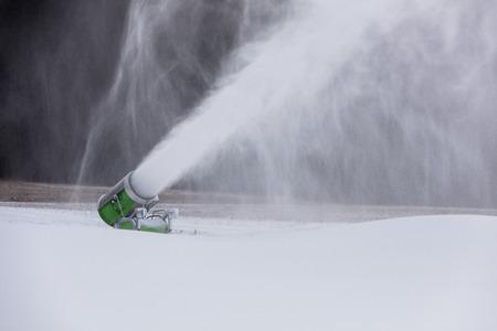 Making snow on the ski track. Artificial snow in the ski resort. Snow machine spews snow. Stock Photo