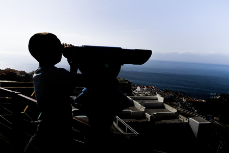 Young boy is looking through binoculars. Sightseeing point. Beautiful views of the city and ocean in the background. Stock Photo