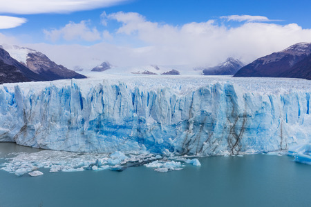 The warming of the atmosphere affects large frozen water supplies and leads to disappearing glaciers and sea level rise. Stock Photo