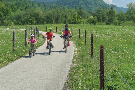 Family active vacation. Green destination. Cycling in the national park. Active lifestyle, healthy lifestyle. Family by the lake, mountains in the background.