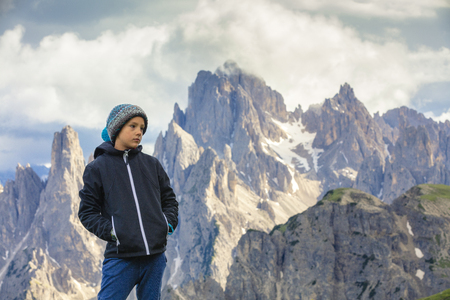 Boy on the trip in to the high mountains. Boy hiking through national park. High mountain peaks in the background.