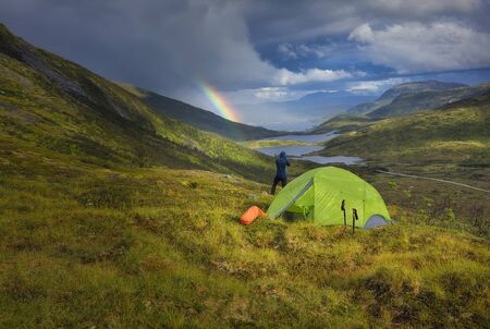 Camping in the nature. Campground in the mountains with the beautiful view over the lakes and river in the background.