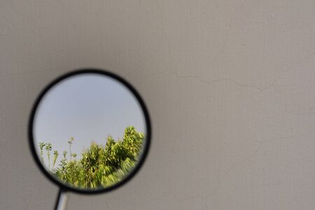 landscape reflected by small circular mirror vehicle, white cement background