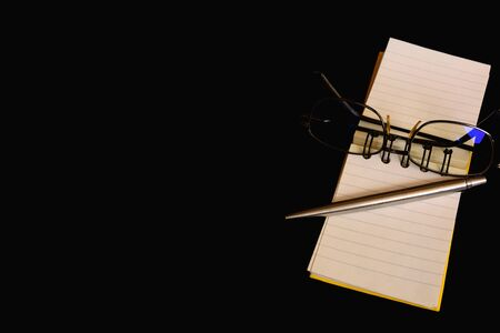 Notebook, pen and eyeglass isolated on black background and copy space.