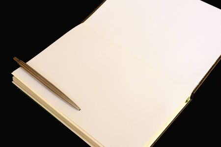 Notebook and pen isolated on black background and copy space.