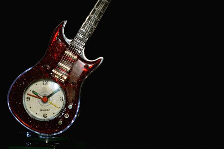 guitar clock resting against black background with copy space