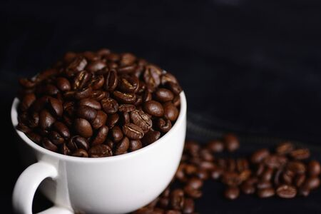 Coffee beans and white mug isolated on black leather background.