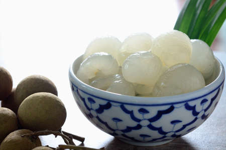 Longan in syrup and pandan leaf on wooden background. Traditional thai dessert.