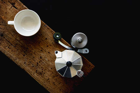 Moka pot and white cup on dark background. Coffee making concept.