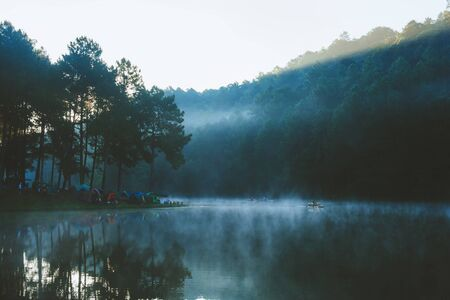 Morning in Pang Ung Lake,North of Thailand, is a tourist place where people come to vacation in the winter. Because of the large reservoir The cold causes steam to rise above the surface. Stock Photo