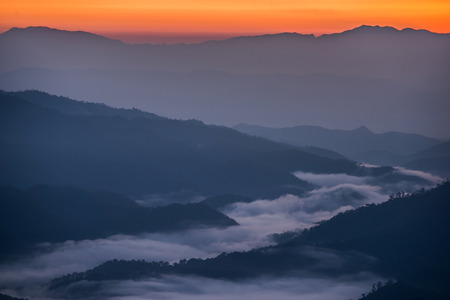 Beautiful sunrise scene with misty in morning in forest valley in Huay Nam Dang National Park. Chiang Mai, Thailand.