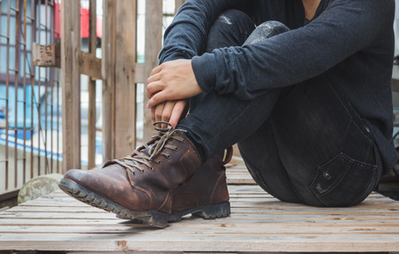 Young fashion man wearing in a black shirt, black jeans and brown leather boots on floor. Old leather boots.