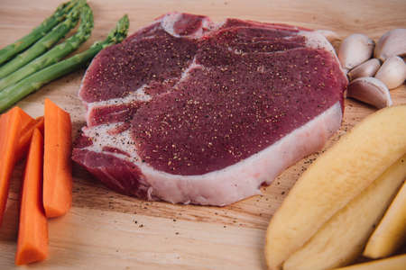 Raw meat t-bone steak with herbs, spices, potato, carrot, garlic and asparagus on a wood background