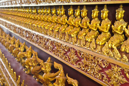 Many small Buddha statue on the wall at  temple, Thailand  photo
