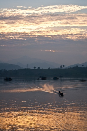 Silhouette of  a boat on a river in the morning  photo