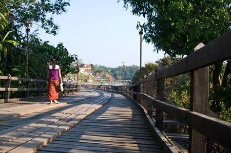 Woman walking on the old wooden bridge in Thailand photo