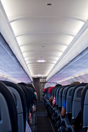 passenger vehicle: Interior of airplane with passengers on seats