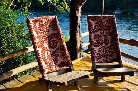 Relaxing chairs near the river with sunlight photo