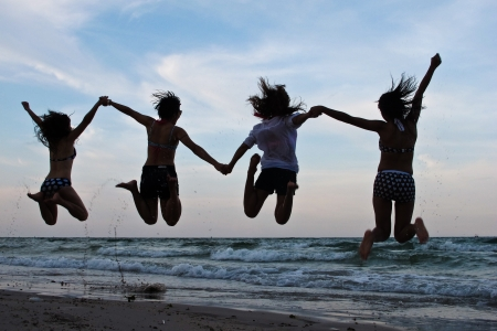 Group of happy women jump on the beach Stock Photo