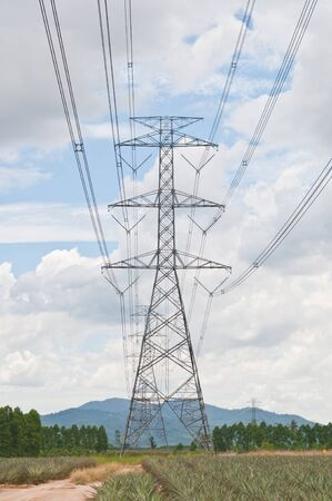 high voltage current: A long line of electrical transmission towers Stock Photo